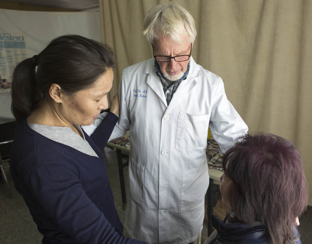 Optician Bob Durkos Praying with Patient 378A9816