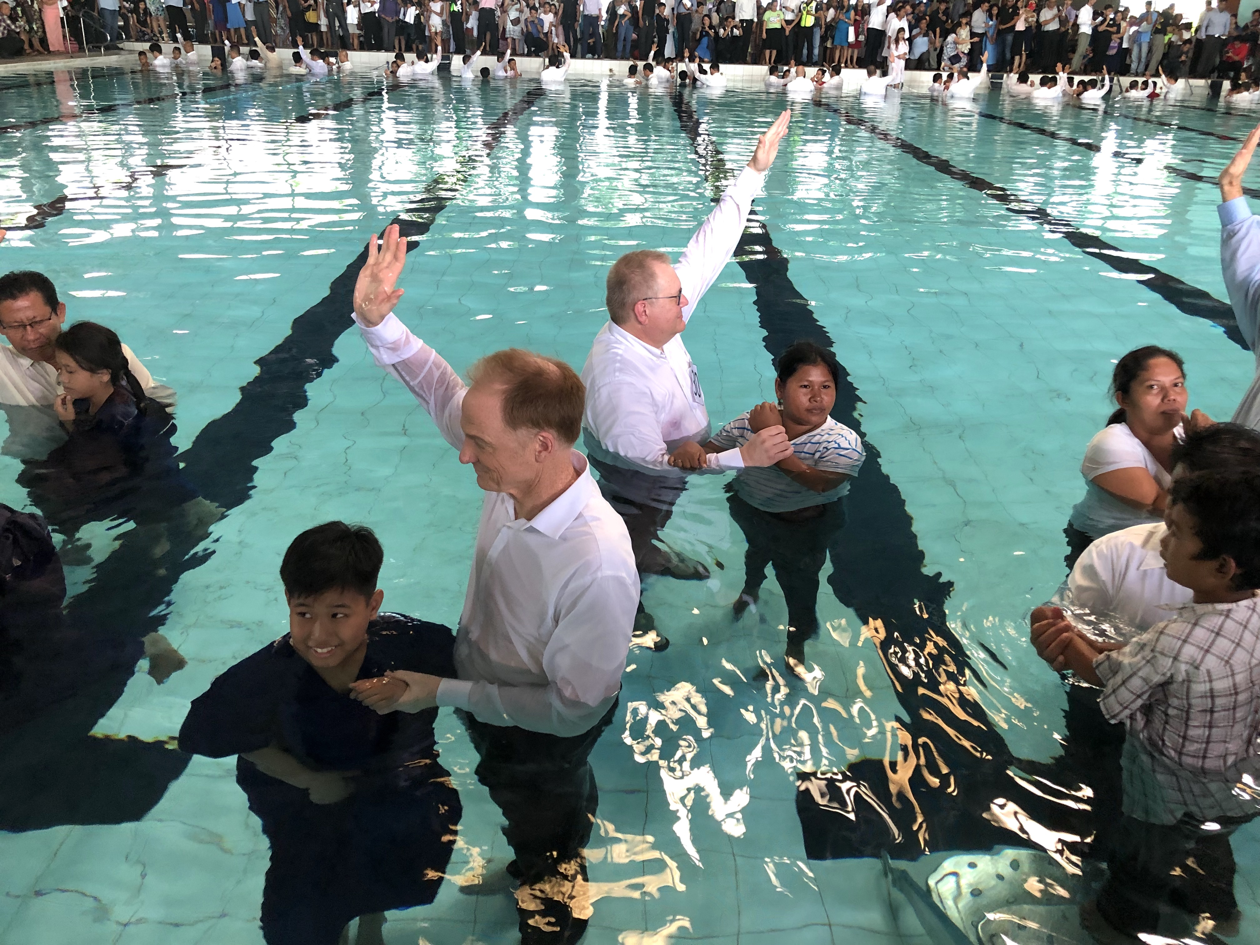 Pastors baptizing many people in a pool
