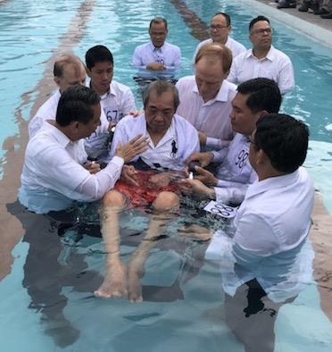 Man in wheelchair being baptized