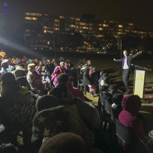John preaching to a crowd at night